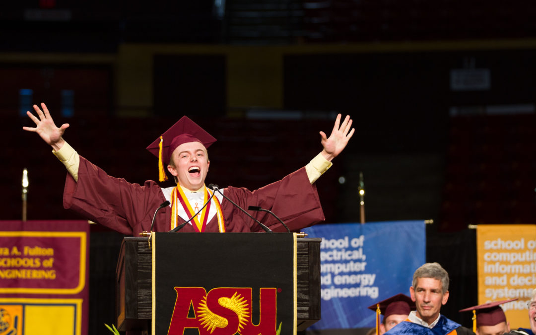 A graduate stands at the convocation podium with his arms held high in celebration