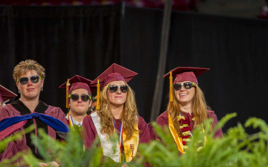 Four graduates sit on stage in full regalia -- and sunglasses!