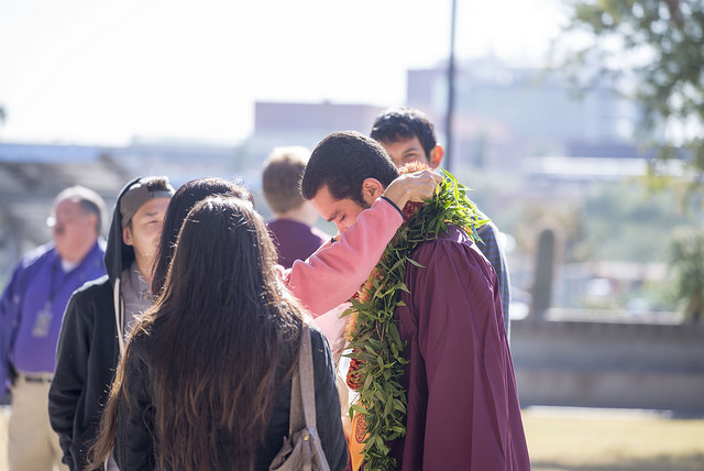 A graduate's monther places a floral lei around her son's neck before graduation