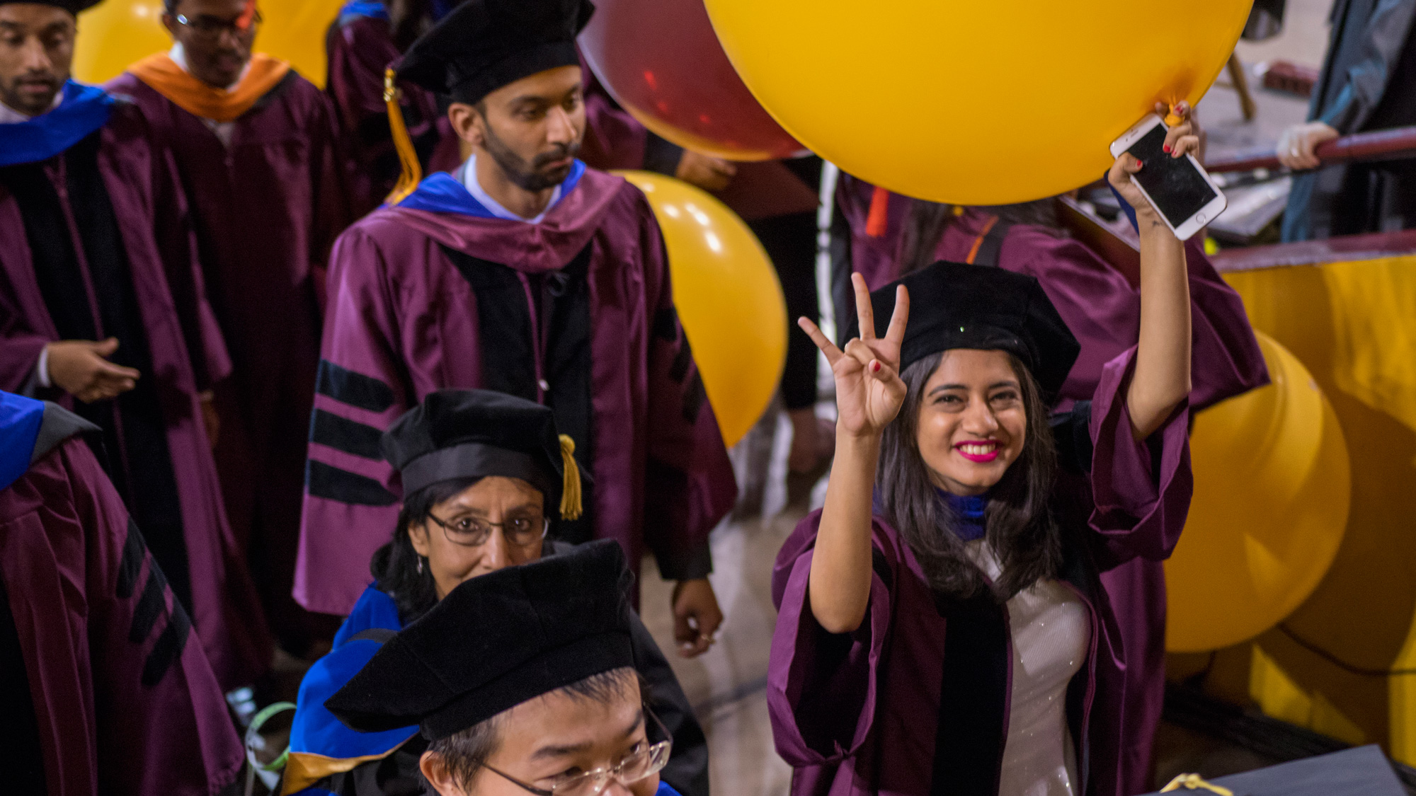 A student holds a balloon in one hand and holds an ASU pitchfork gesture in the other, as she smiles leaving Convocation
