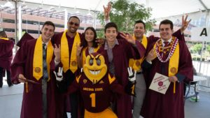 a group of graduates pose with Sparky for a photo at Convocation check-in