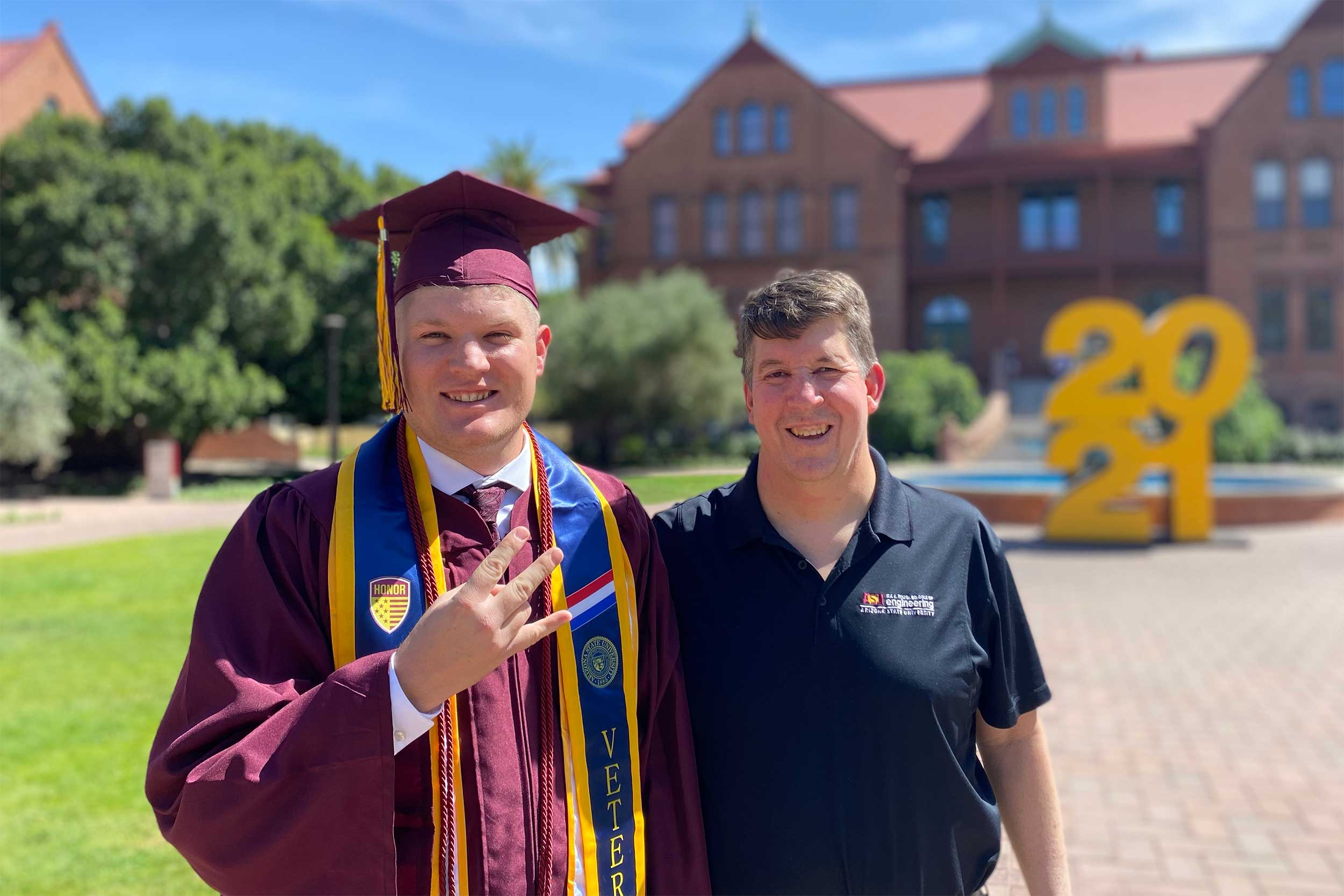 Fulton Schools Graduate Bobby Hudson, in his full regalia, including his veteran's stole, stands with his father, Rick, a Fulton Schools alumnus, in front of Old Main on ASU's Tempe campus
